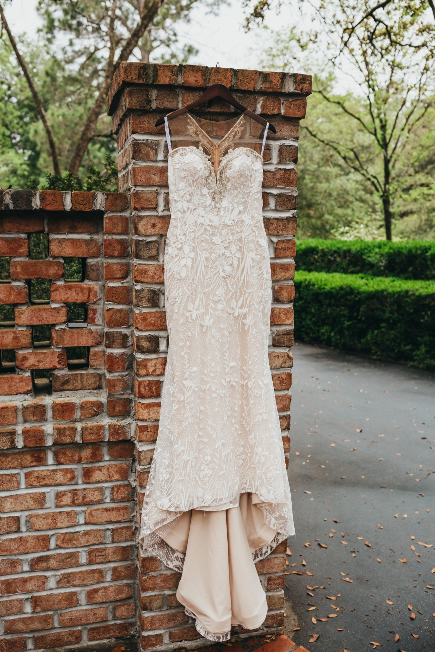 stunning off-white wedding dress hanging from a red brick column