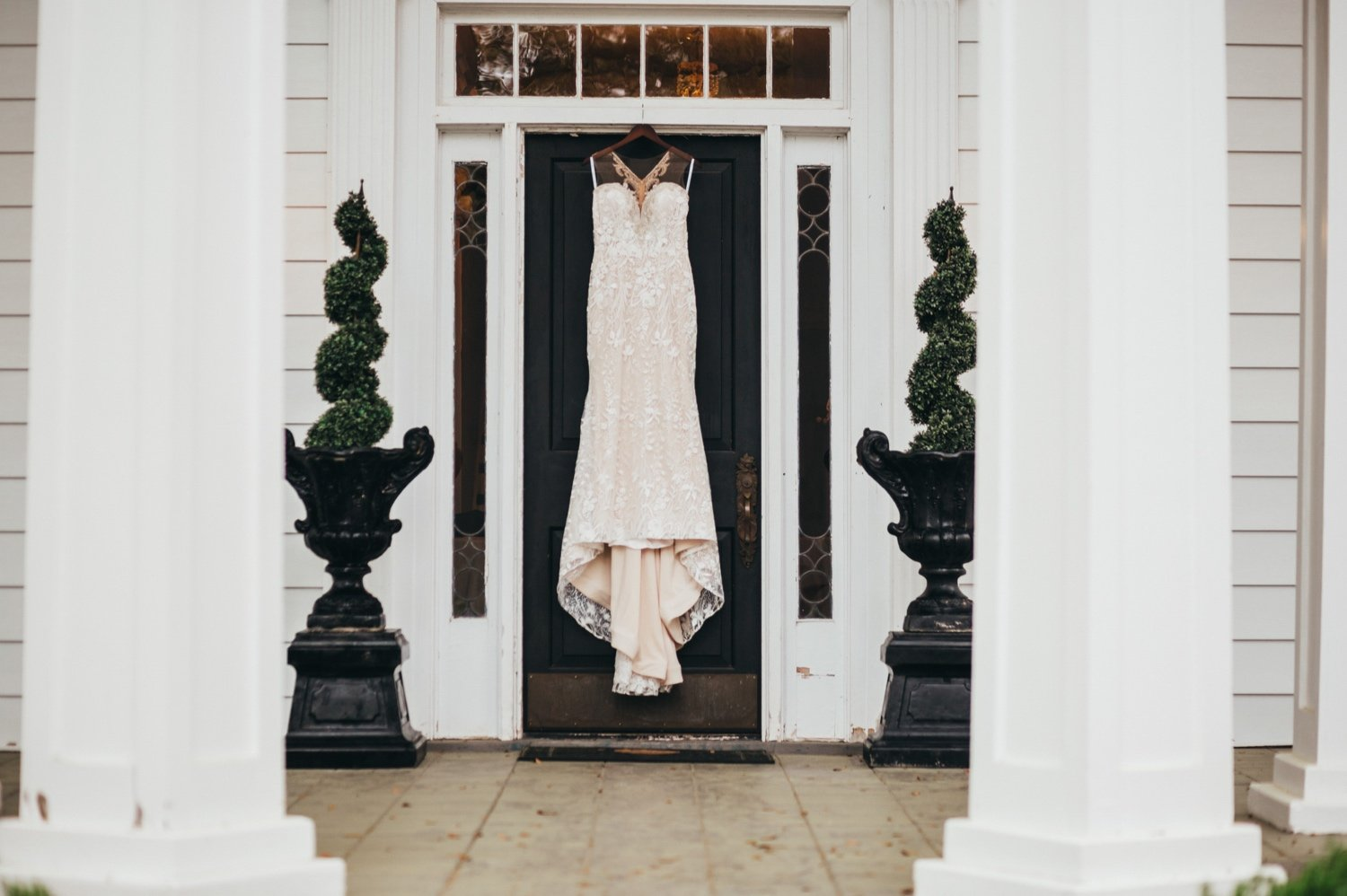 wedding dress hanging on the front door of the venue