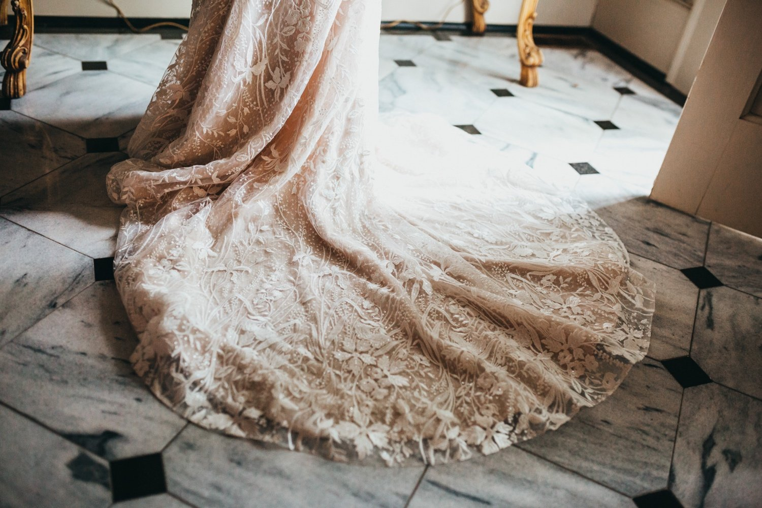 beautiful details on the bottom of the wedding dress fanned out in the marble tile hallway