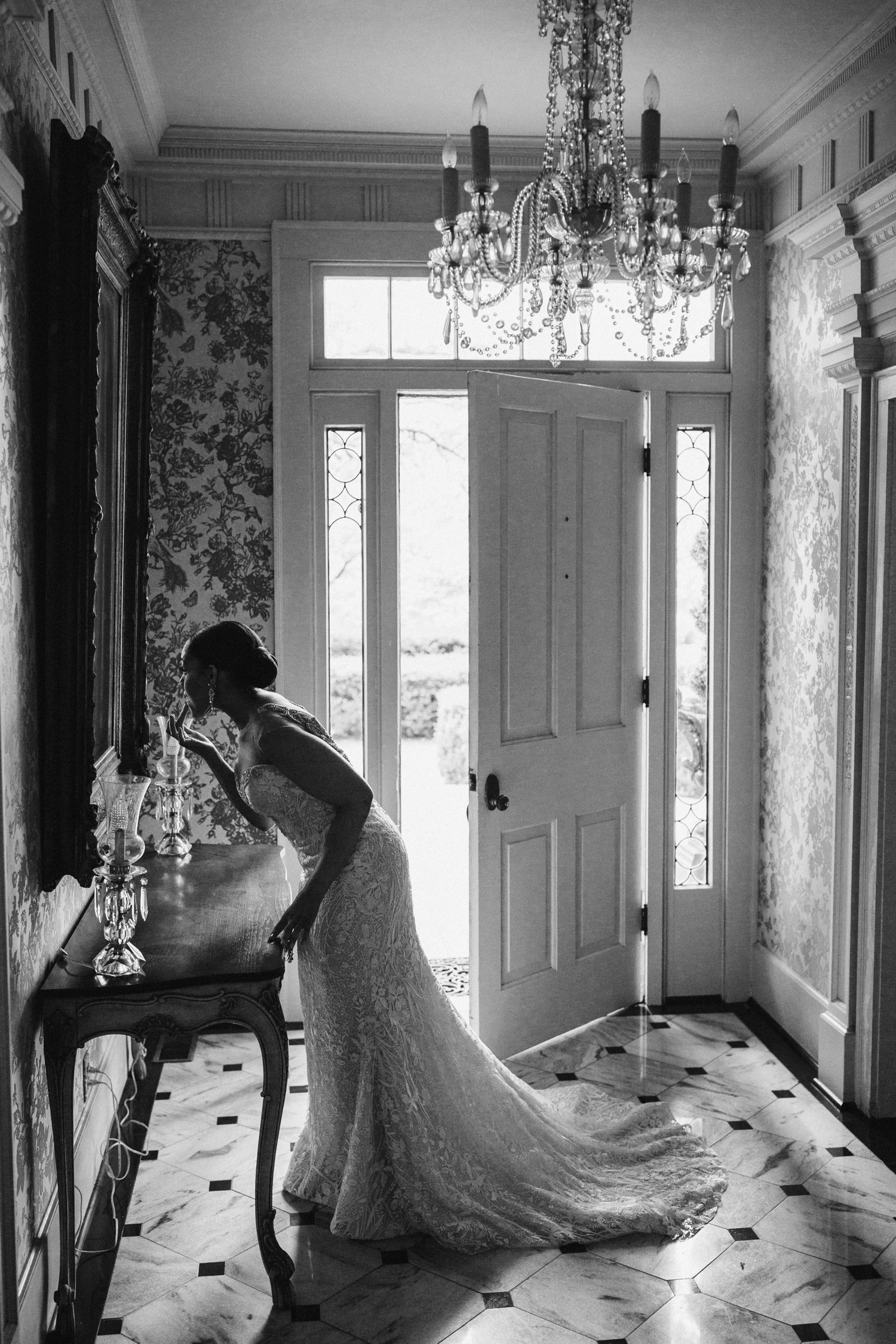 bride applying final touches to makeup in hallway mirror