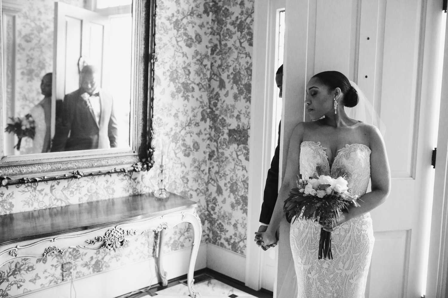 bride and groom having a first touch moment in the front hallway
