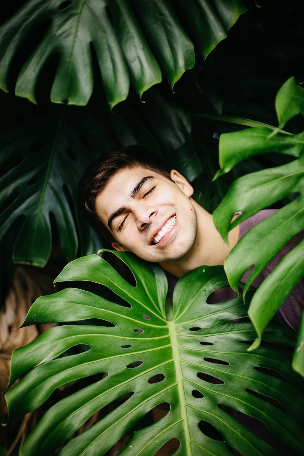 cute boy in the middle of large monstera leaves. LOL. NYC Wedding Photographer. Destination Wedding Photographer, Destination Wedding Photographers in NYC, NYC Destination Wedding Photographer, Brooklyn Destination Wedding Photographers, Brooklyn Destination Wedding Videographers, NYC Destination Wedding Videographer