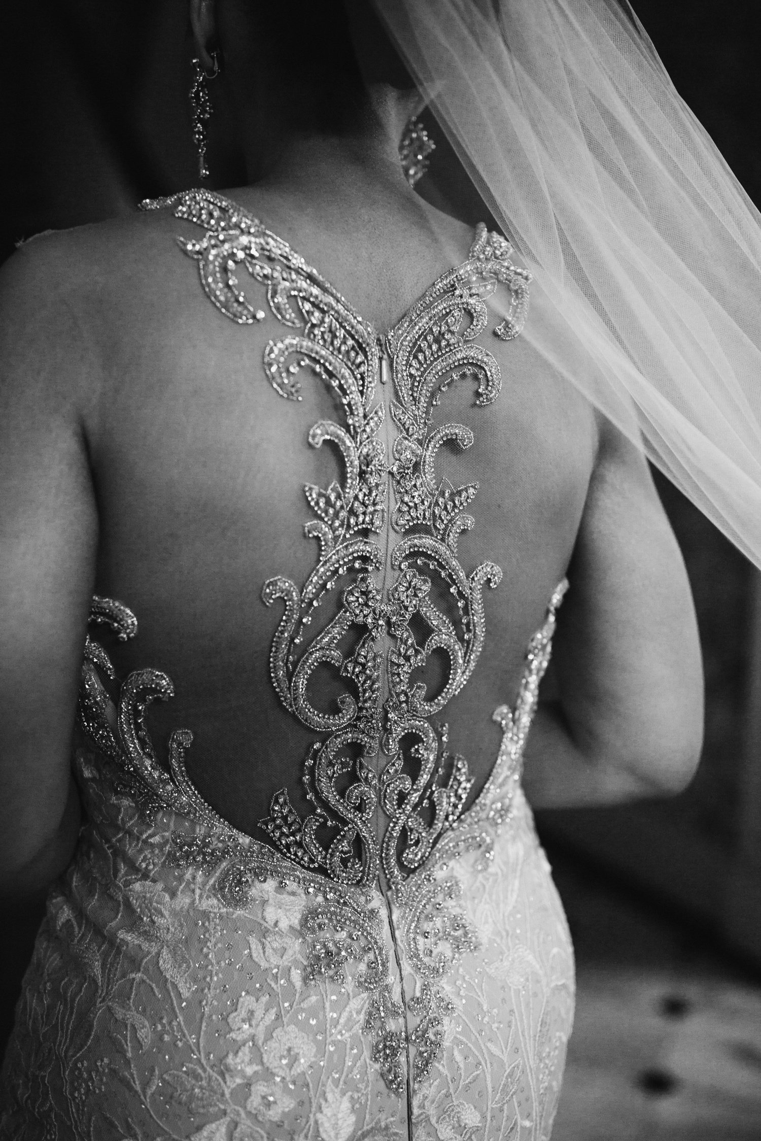 intricate details of the brides dress with jewels on the backside