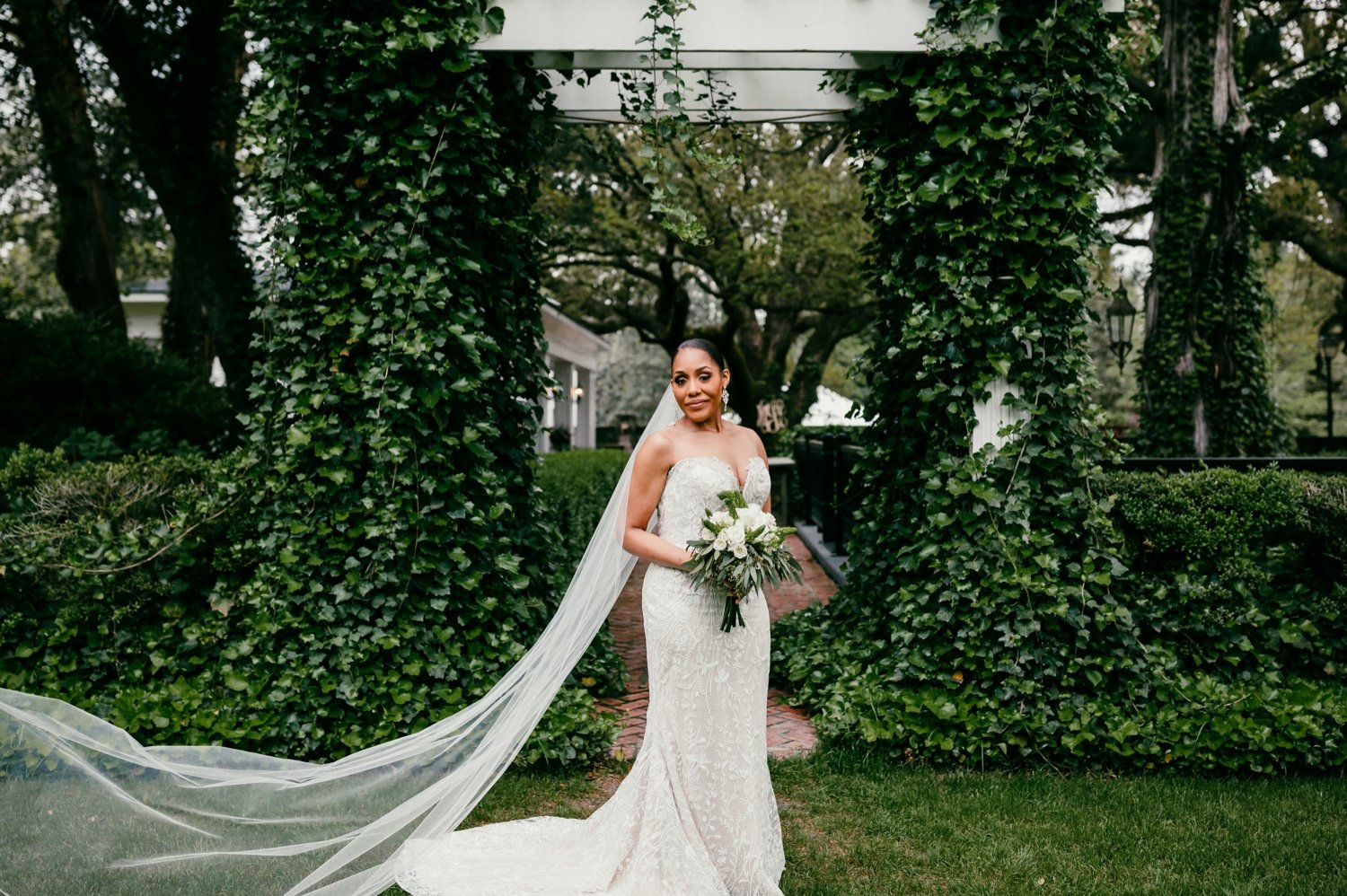 photo of the bride in her wedding dress holding bouquet of white flowers with greenery behind her