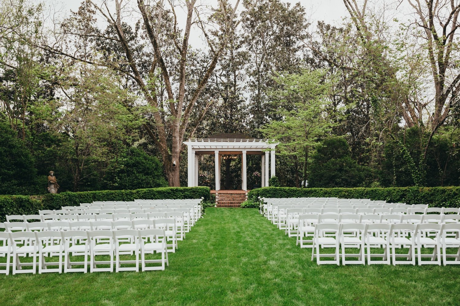 photo of the outside ceremony setup. White chairs on a green lawn and brick steps leading up to a white terrace.
