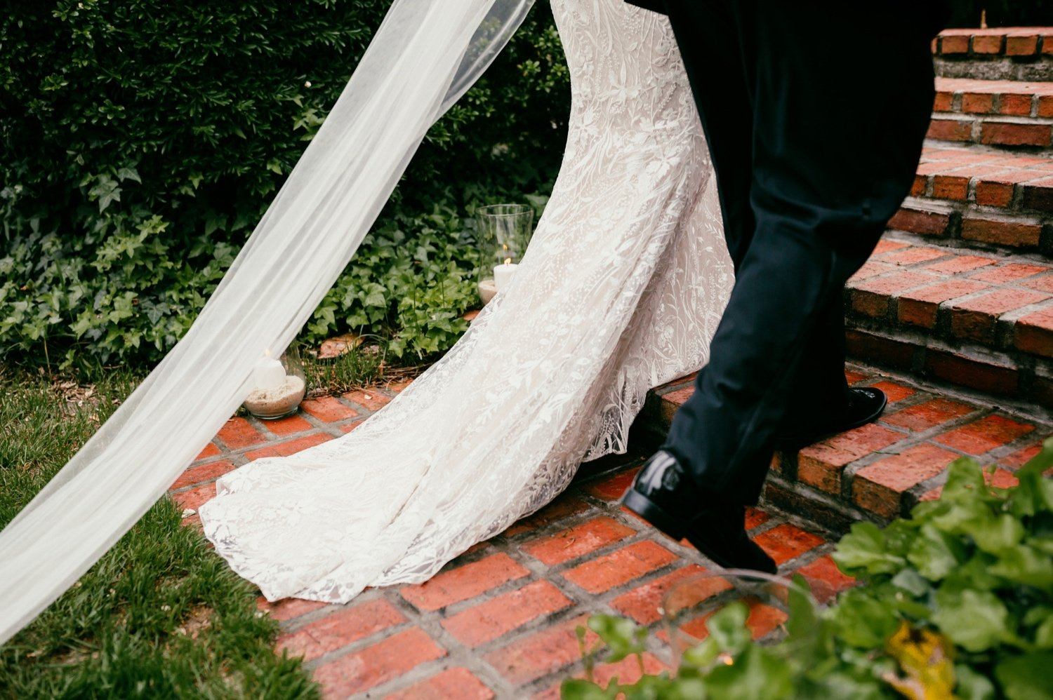 closeup of the dress flowing across the brick steps as bride walks toward broom