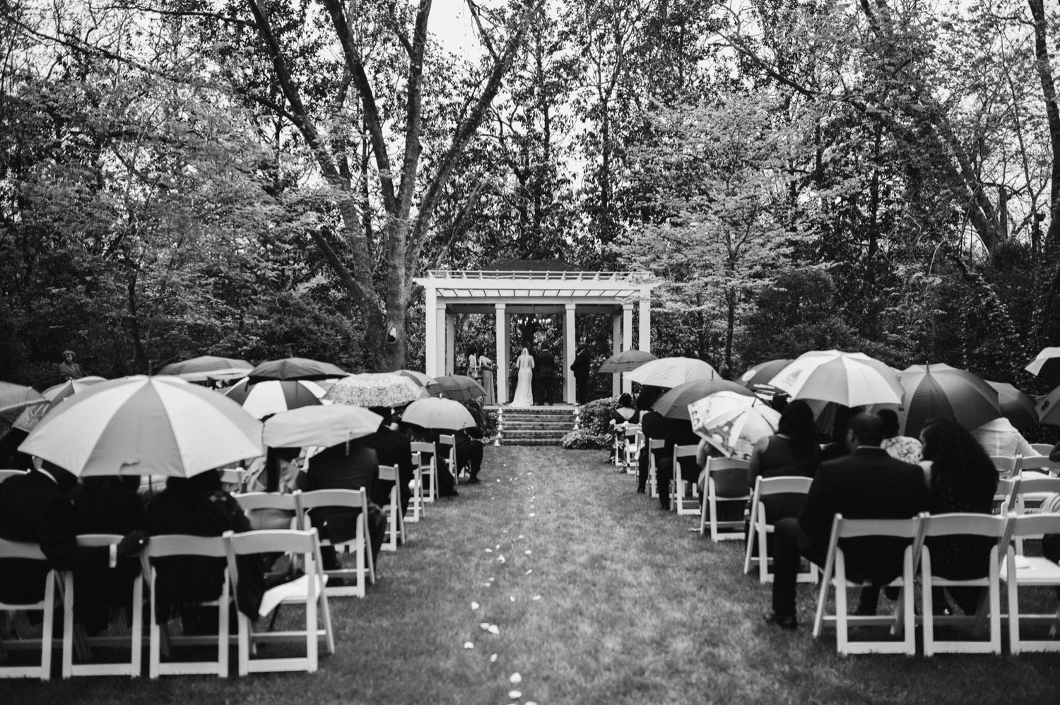 wide shot of the ceremony as guests use umbrellas for the light rain