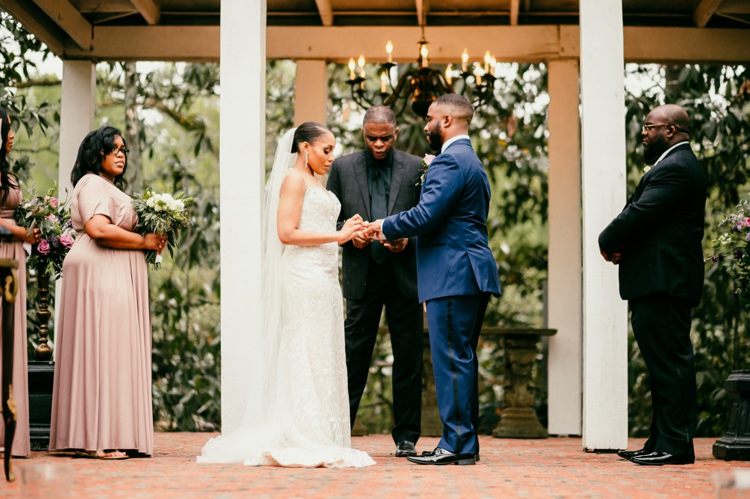 bride places ring on grooms hand during the ceremony