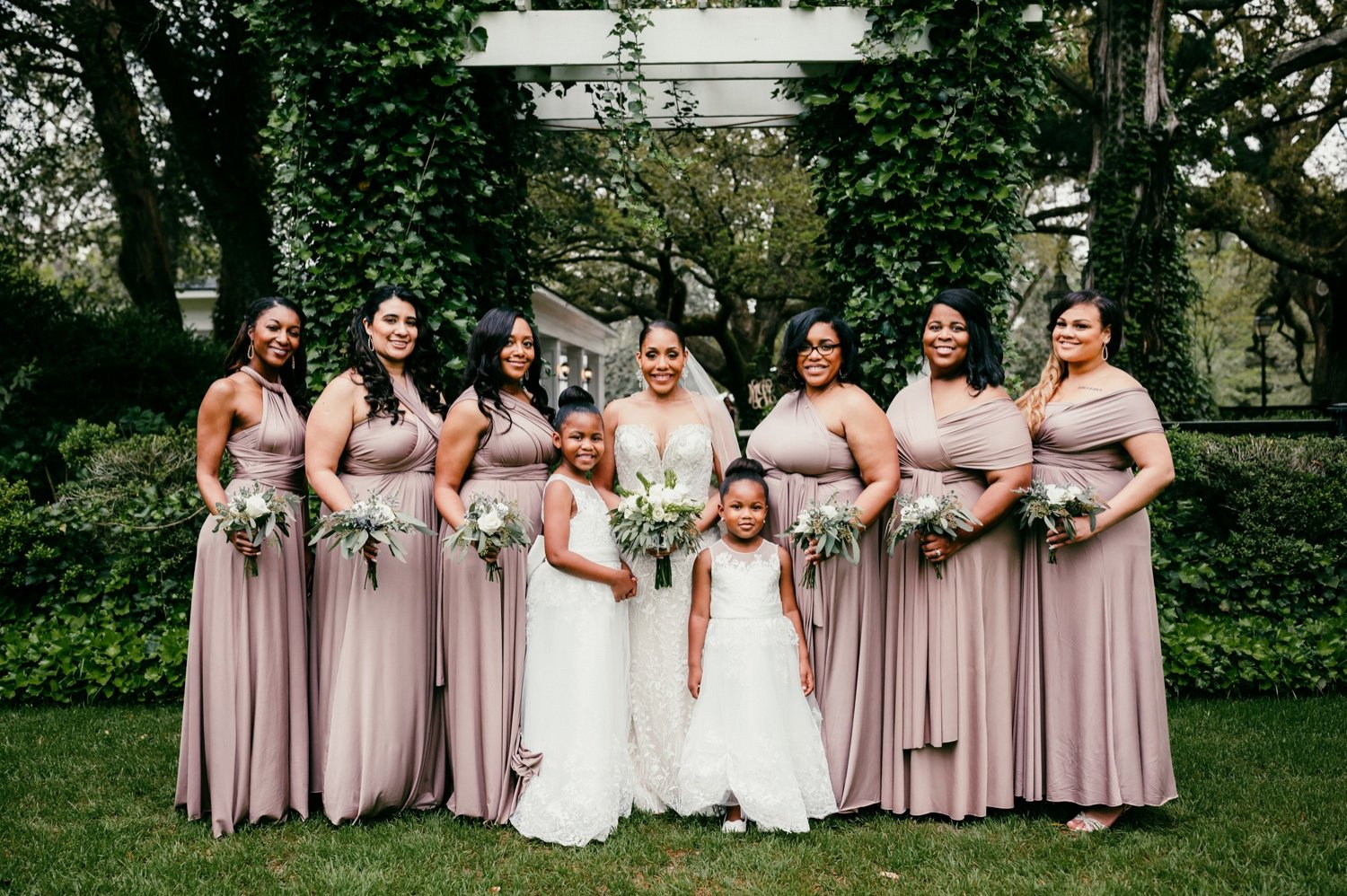 photo of all the bridesmaids in their blush pink dresses with the bride and flowergirls