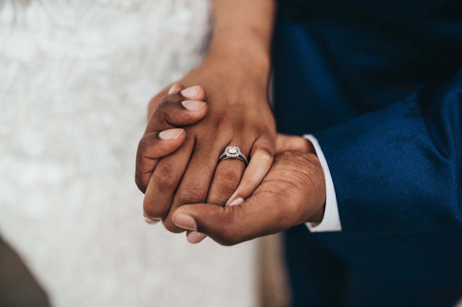 closeup of hands holding with the brides wedding and engagement ring showing