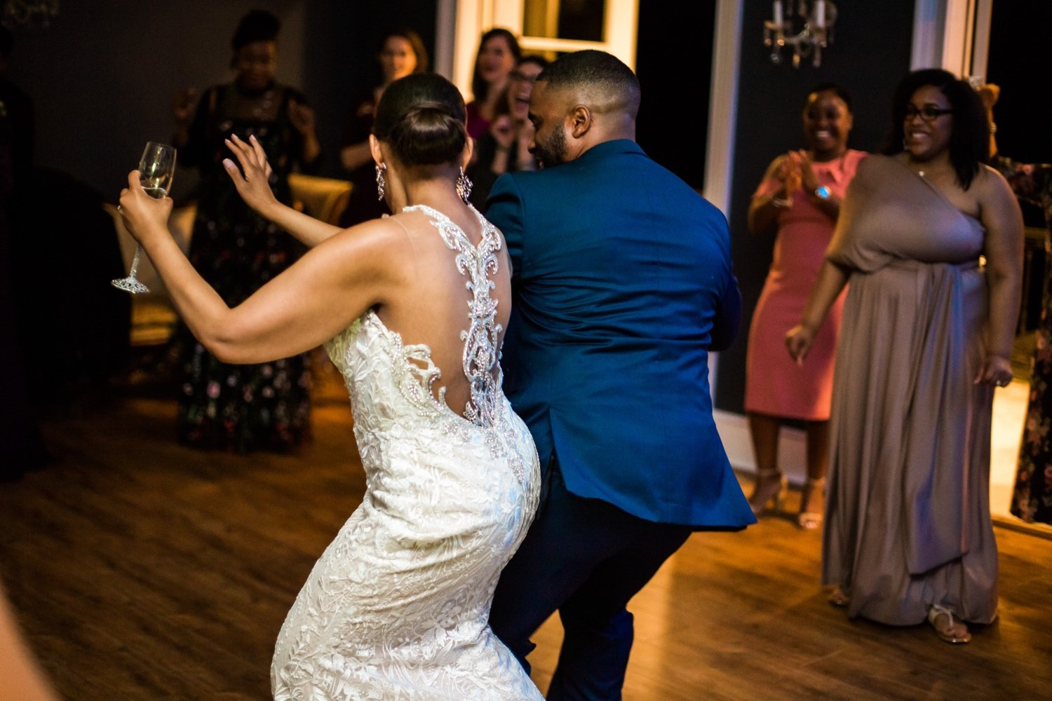 bride and groom bumping waists as they dance to music during the reception