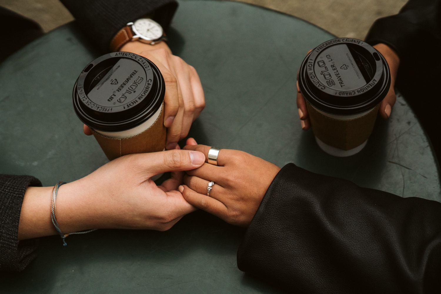 photo of fiance's holding hands across a table. Woman has engagement ring on her hand.