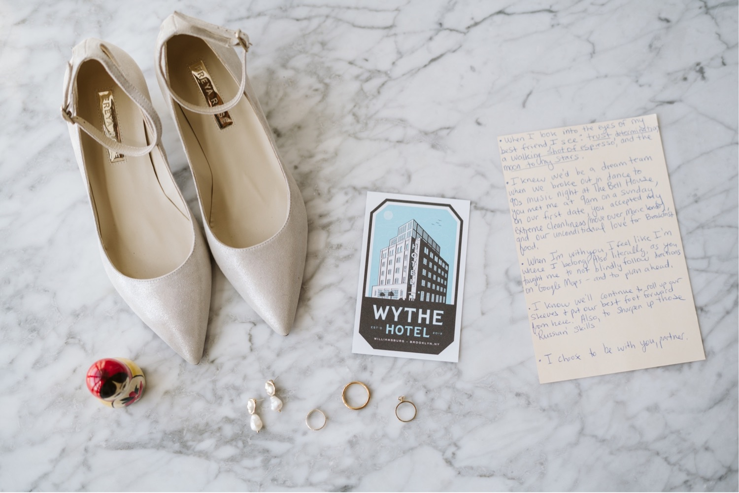 Closeup of the Freya Rose London wedding shoes laid out with wedding details like vows, wedding rings, and the wythe hotel welcome card