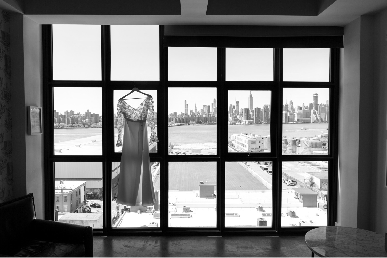 the bride's wedding dress a Rime Arodaky Paris wedding gown hanging on the wythe hotel windows with the manhattan new york city skyline in the distance