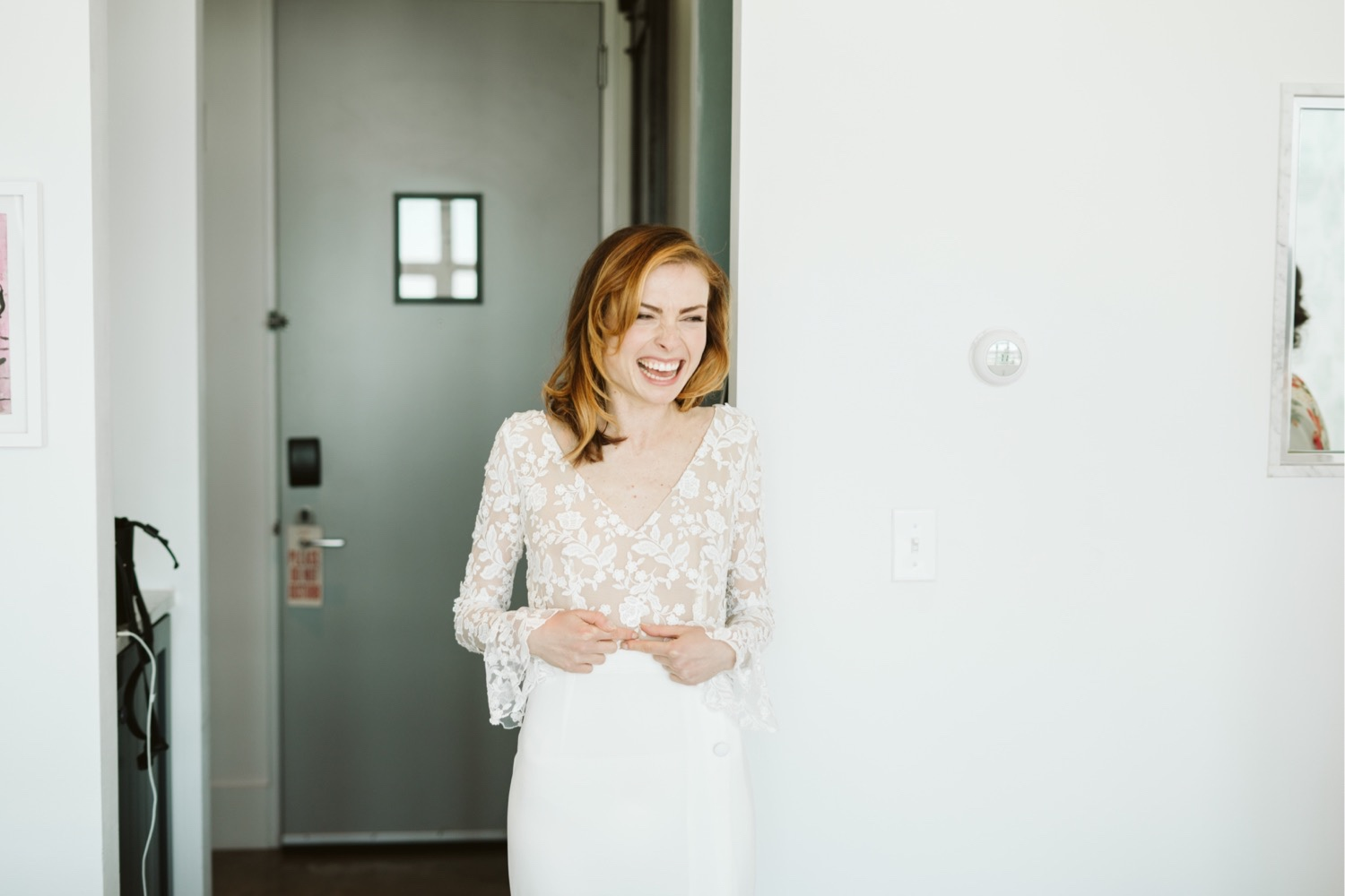 the bride in her rime arodaky wedding gown with sleeves and lace with a sheer bottom half and 3 buttons at midsection, showing her bridesmaids the dress for the first time