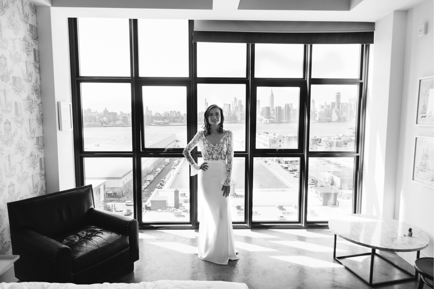 beautiful posed photo of the bride centered in the wythe hotel room windows with the manhattan city skyline visible in the distance
