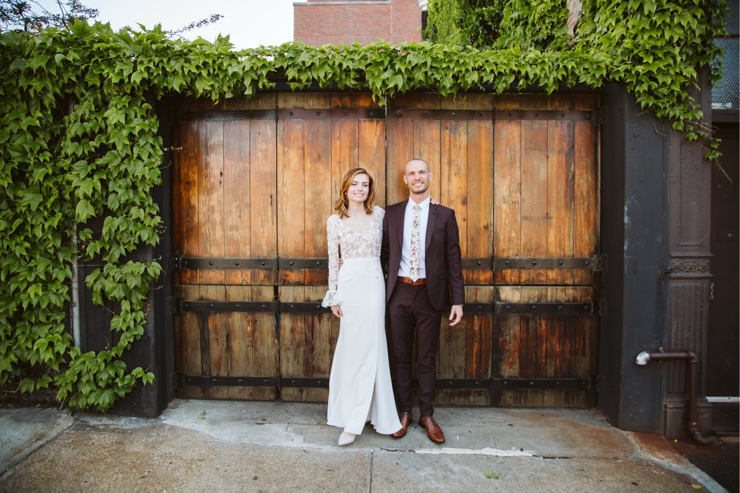 the bride and groom centered in front of the large wooden doors surrounded by green plants at the wedding venue in brooklyn - Aurora Ristorante