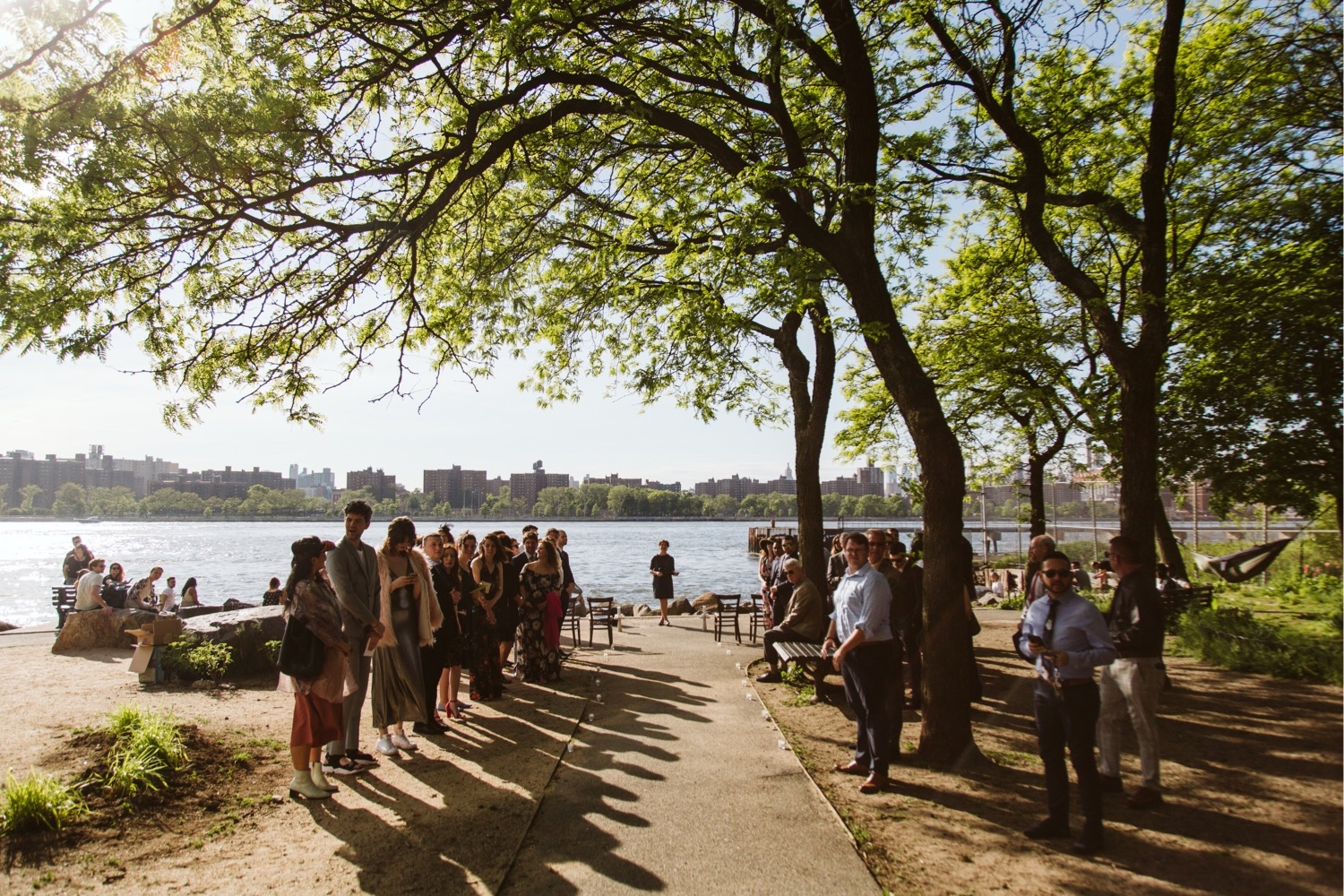 The guests for the ceremony are gathered at grand ferry park, a large tree shades all of them with the waterfront in the background.