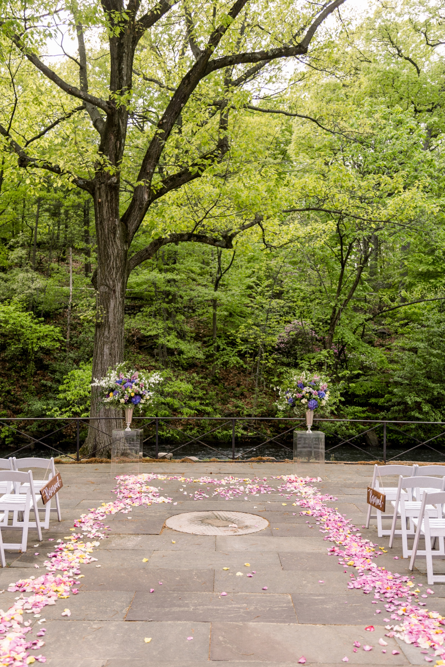Ceremony setup with floral columns and chairs prior to the ceremony at stone mill in NYBG