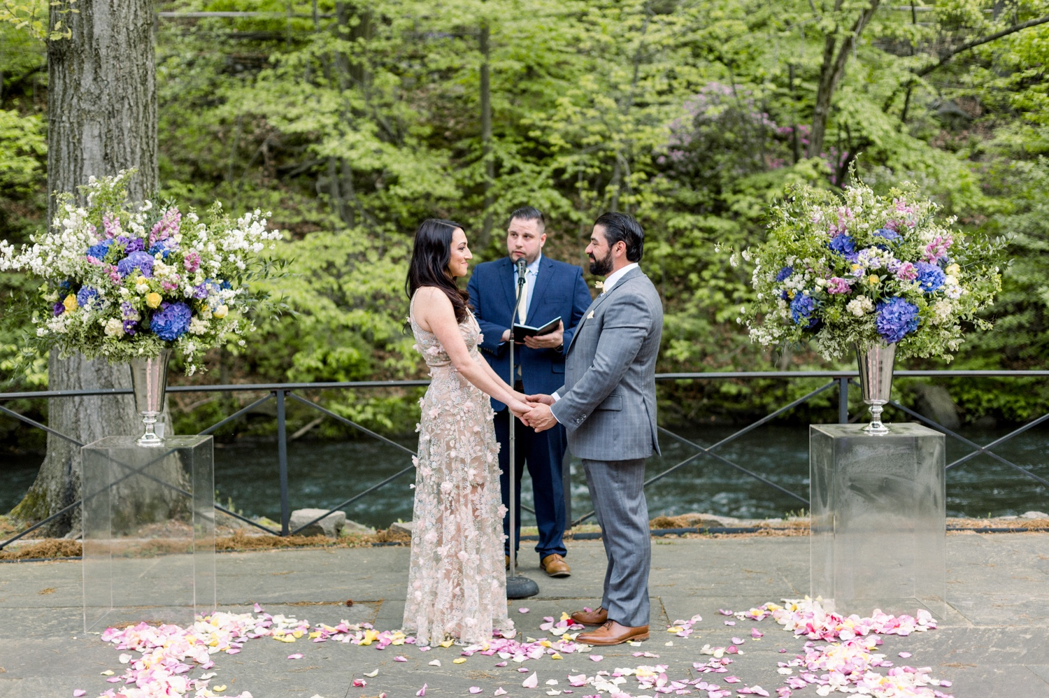 bride and groom exchanging vows during the ceremony at stone mill in NYBG
