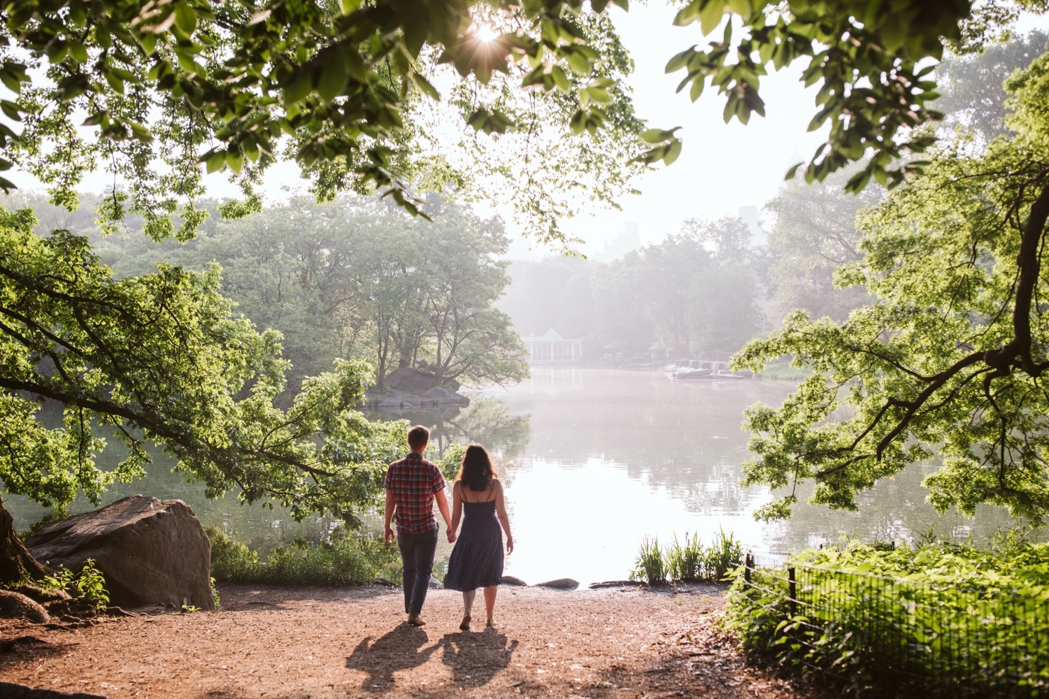 couple walking in central park toward the water near the boathouse
