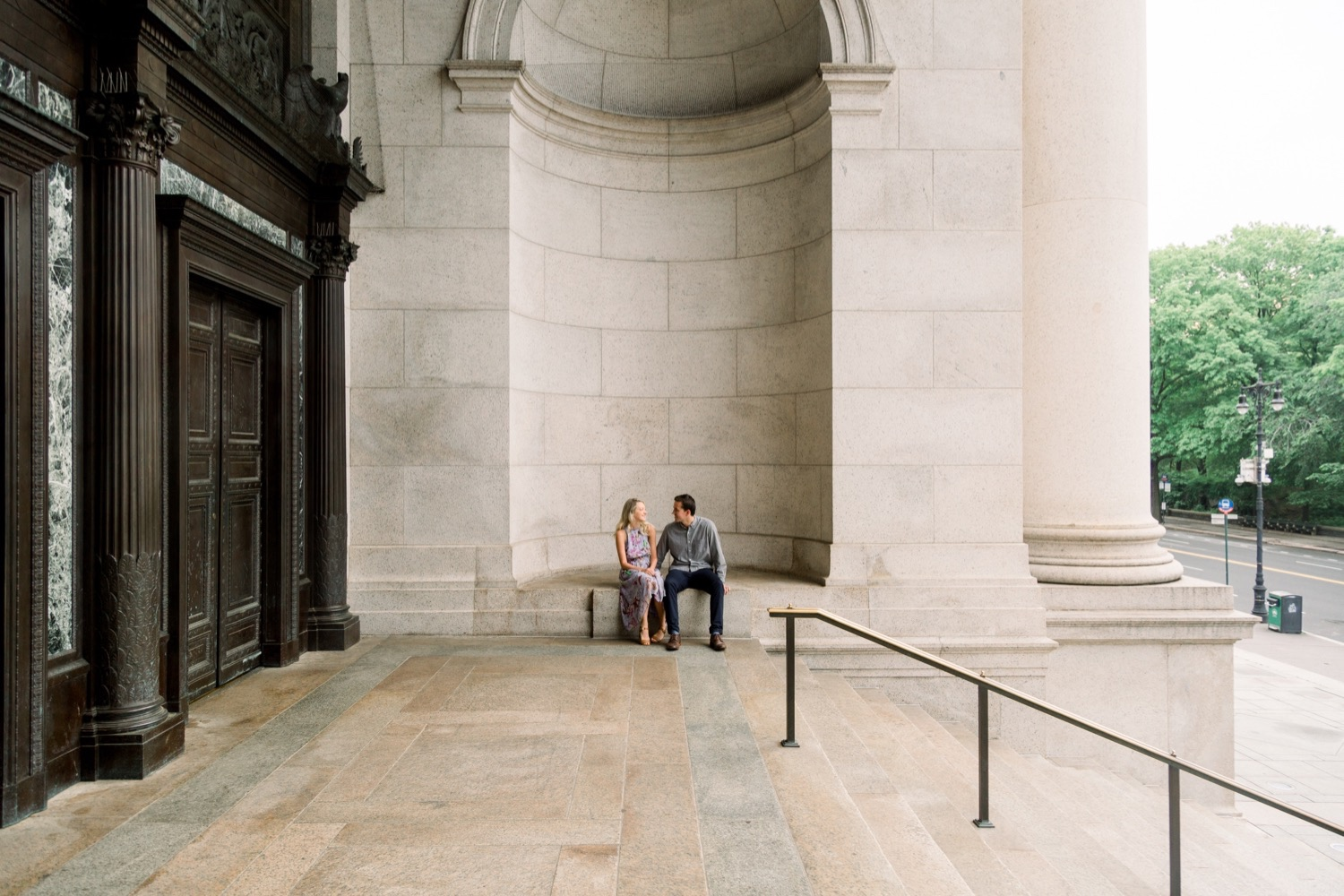 Couple sitting in the alcove at the entrance of The American Museum of Natural History