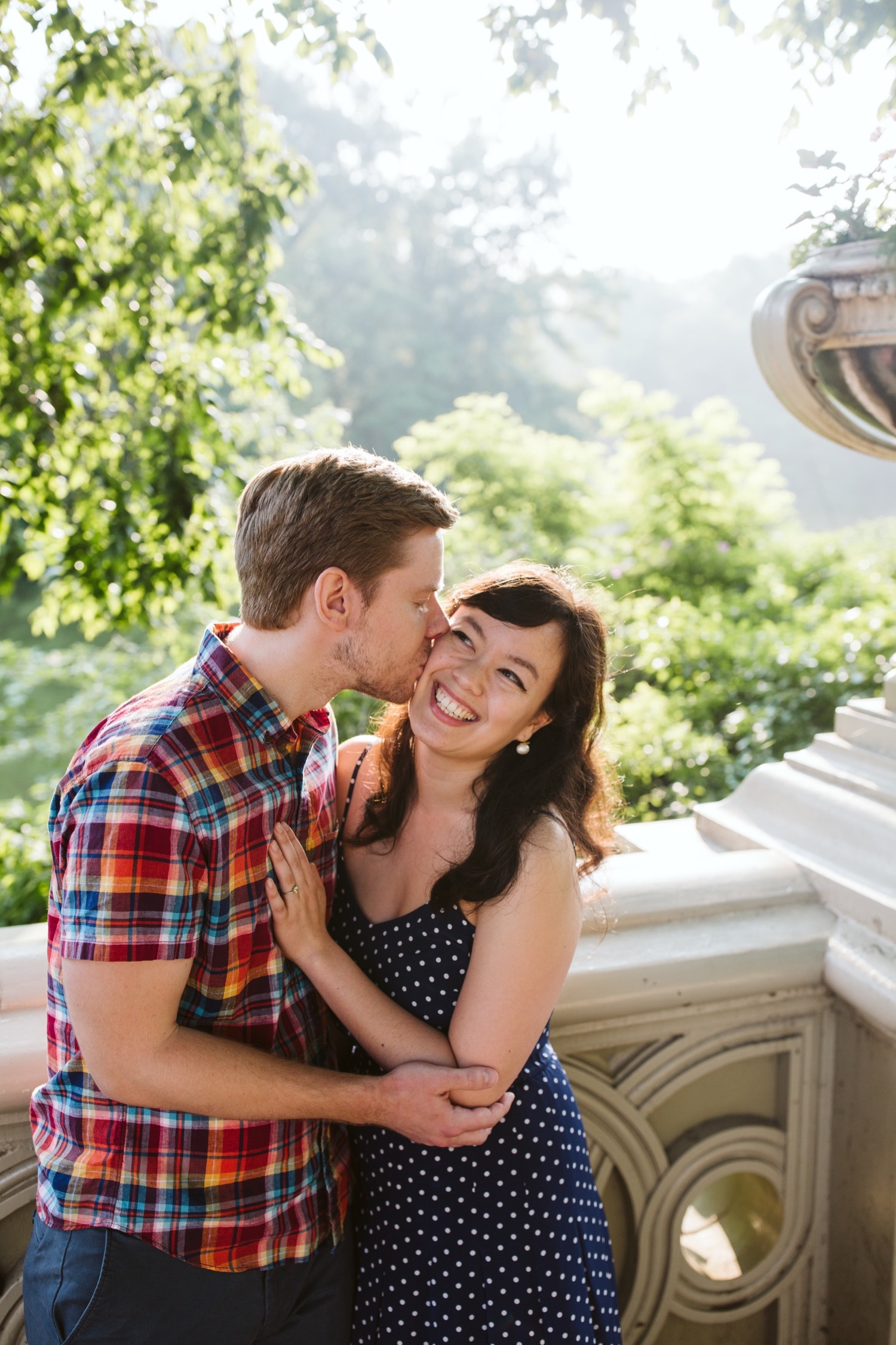 man kissing woman on cheek at bow bridge during engagement session