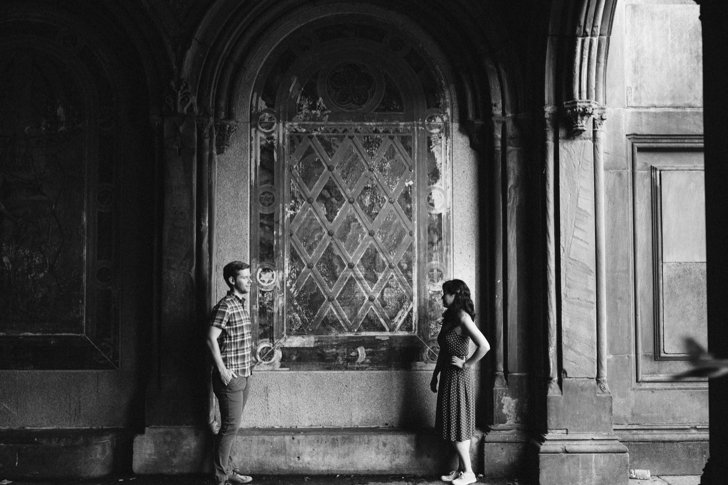 black and white photo of the couple standing across from each other inside bethesda terrace, a bird swoops by in the photo.