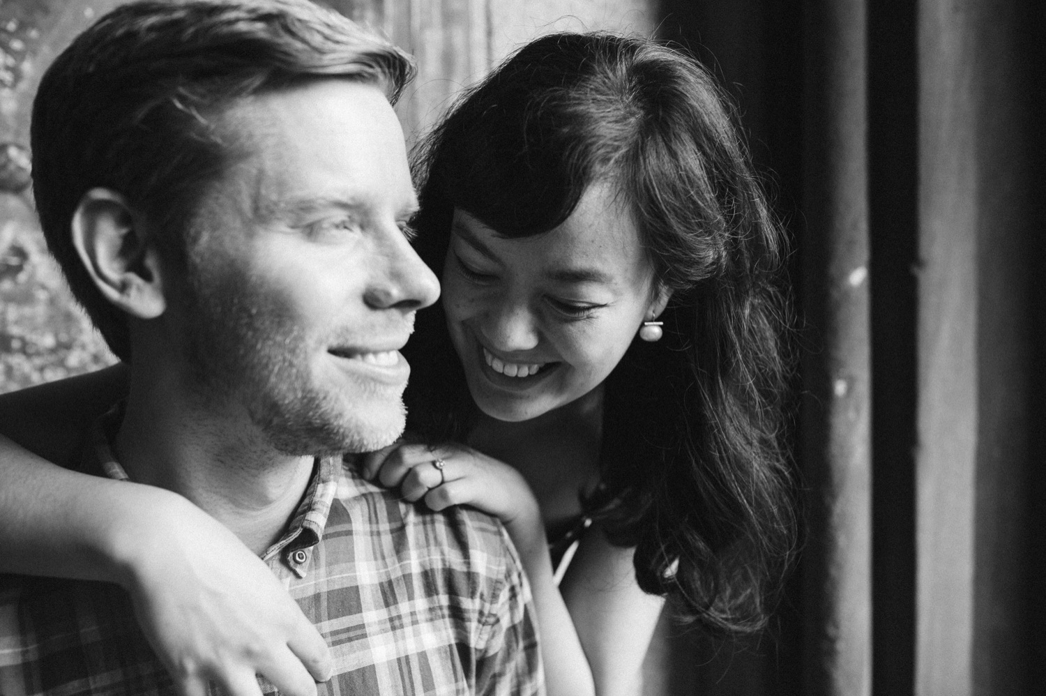black and white photo of engaged couple. She is wrapping her arms around his shoulders whispering things in his ear