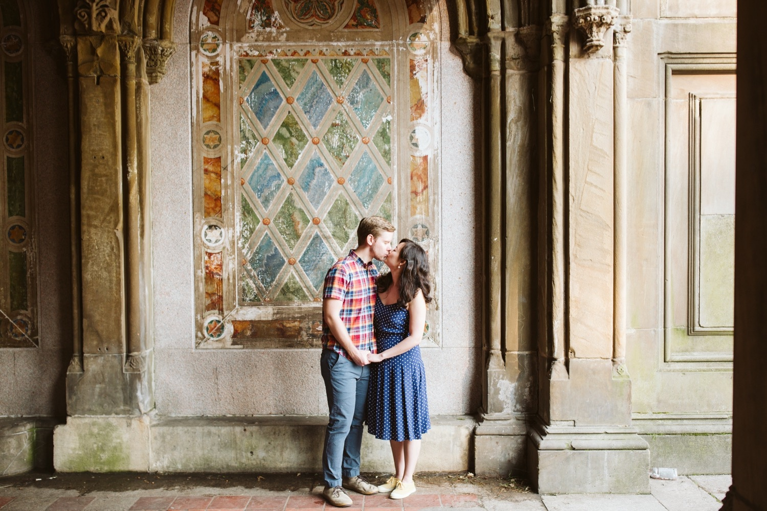 engaged couple kissing and standing closely in front of the painted checkered bethesda terrace wall, a popular central park engagement session spot