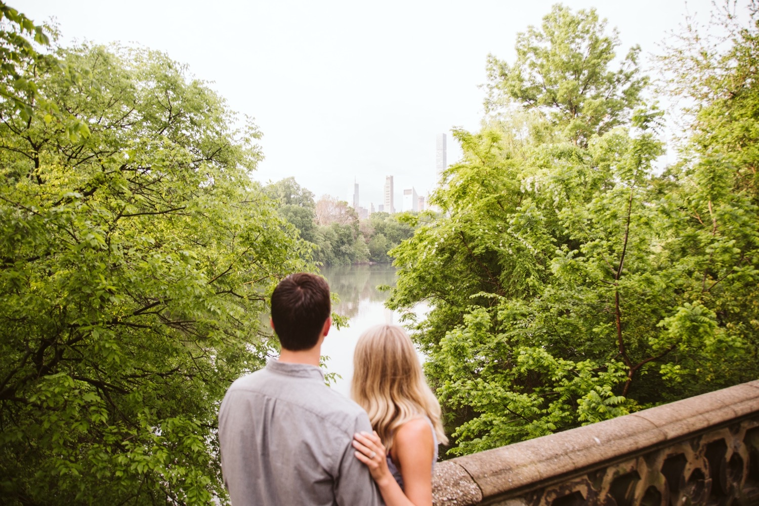 Couple looking out onto the lake toward Bow Bridge in Central Park