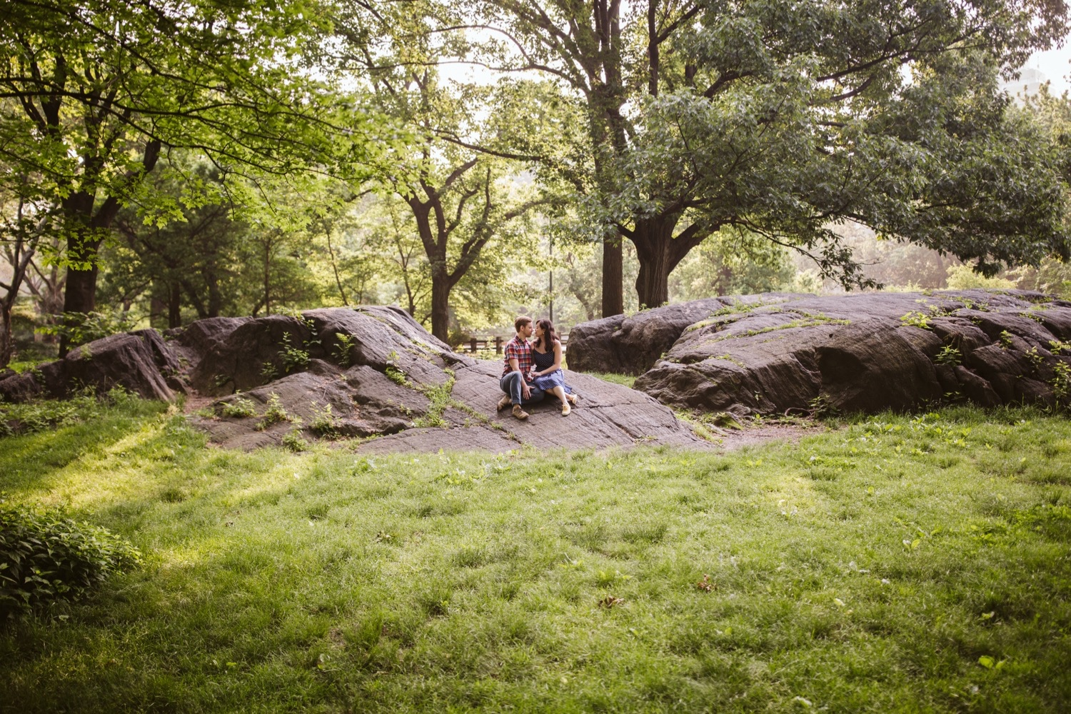 a wide shot of an engaged couple sitting closely on a rock in central park