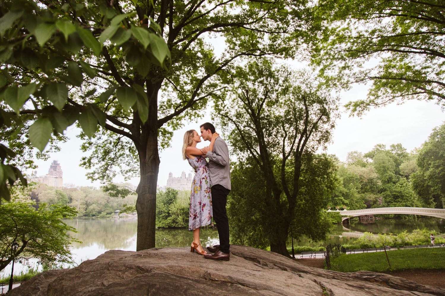 couple standing on top of a large rock for their central park engagement photos