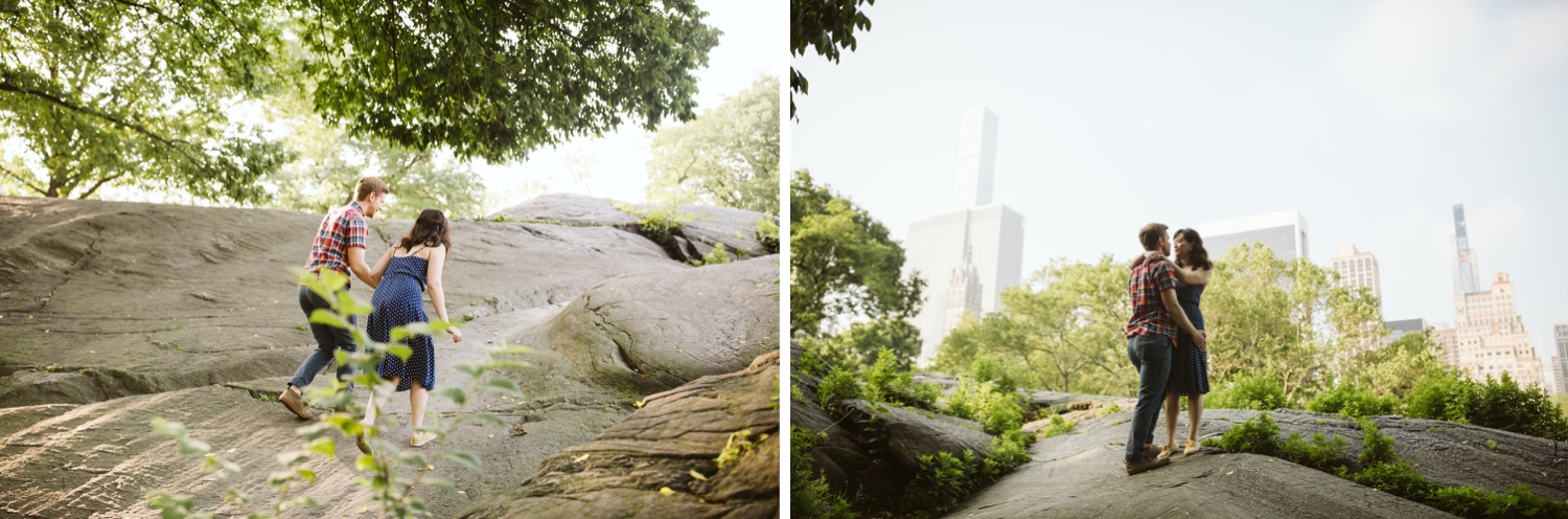 wide shot of new york city skyline from central park rocks, where the couple is kissing.