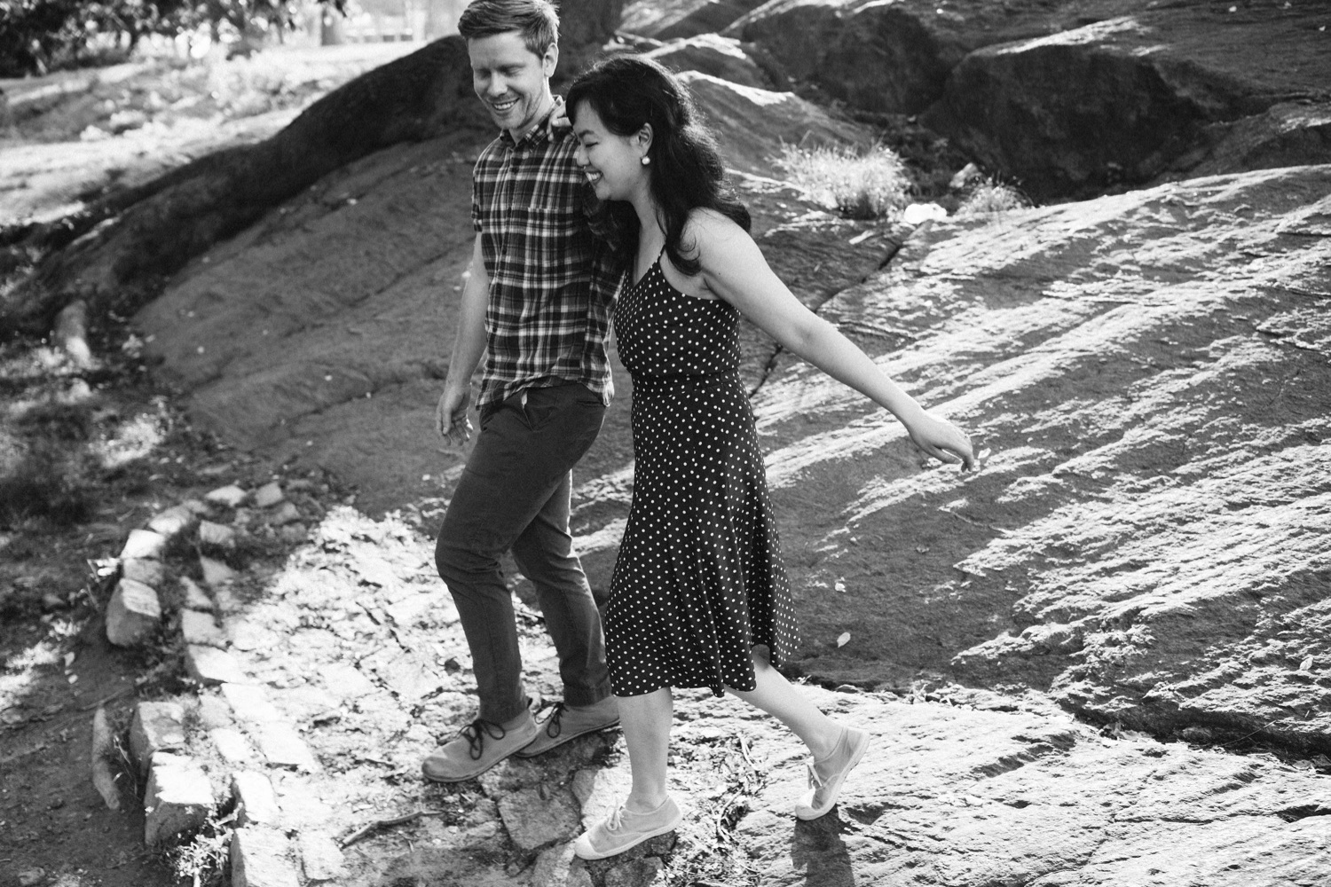 couple is walking down from the large rocks, to continue their engagement session