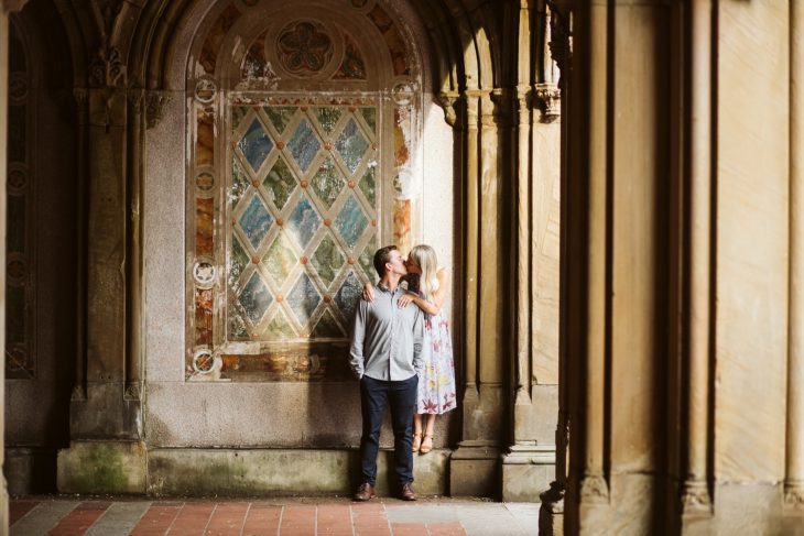 Couple kissing inside of bethesda terrace in front of the colorful checkered painted wall.