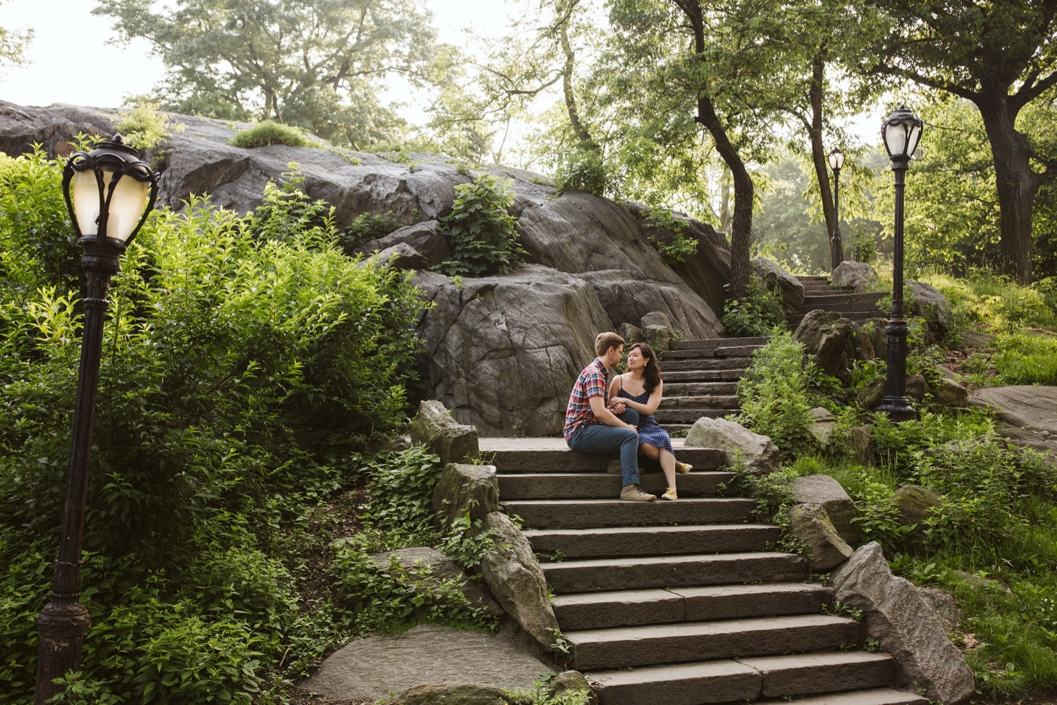 the engaged couple sitting on the top of a staircase on the rocky area.