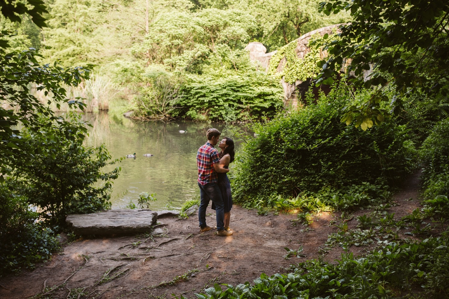 the engaged couple in a secret spot at central park for engagement photos, the gapstow bridge is in the background