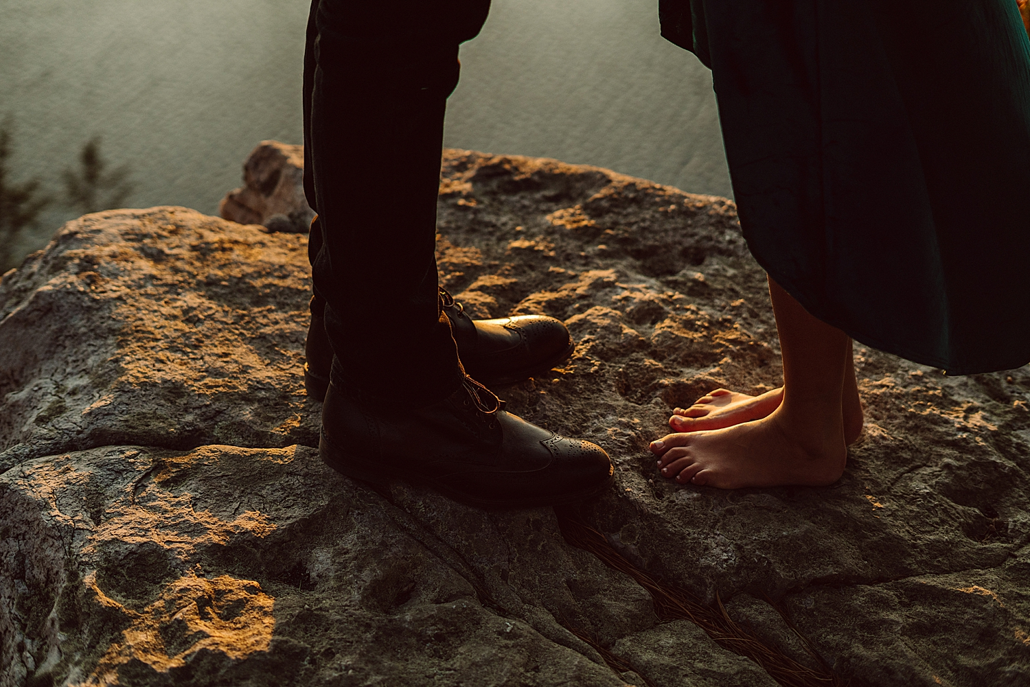 close up of couple's feet as they embrace on the cliffside overlooking Minnewaska Lake