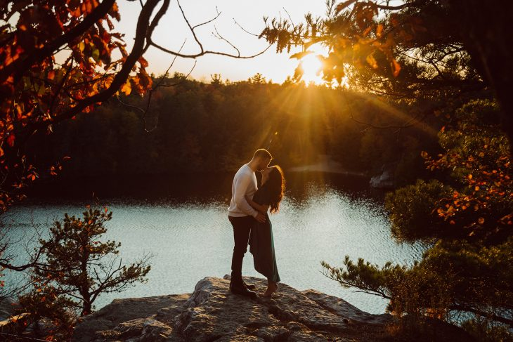 engaged couple embracing in front of lake Minnewaska for engagement session