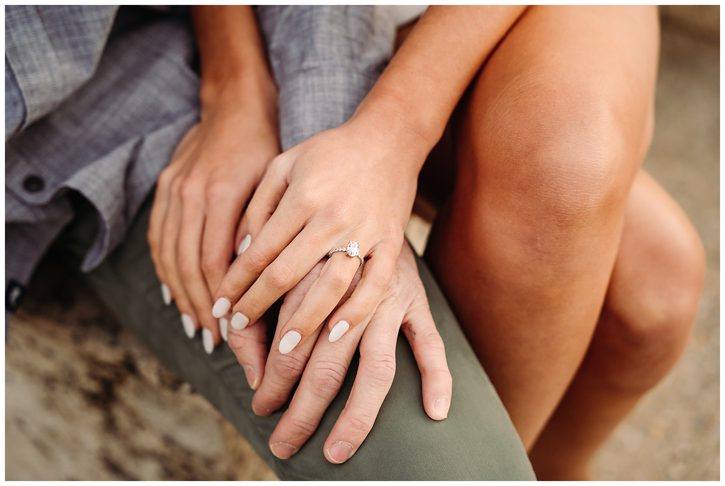 couple holding hands with engagement rings showing